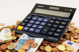 Taschenrechner liegend auf Münzen